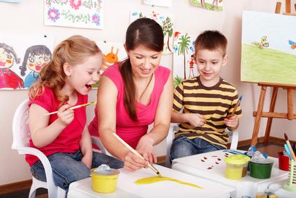 Kindergärtnerin malt mit Kindern ein Bild
